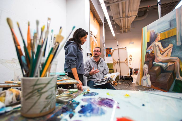 Student and instructor talk in an art lab