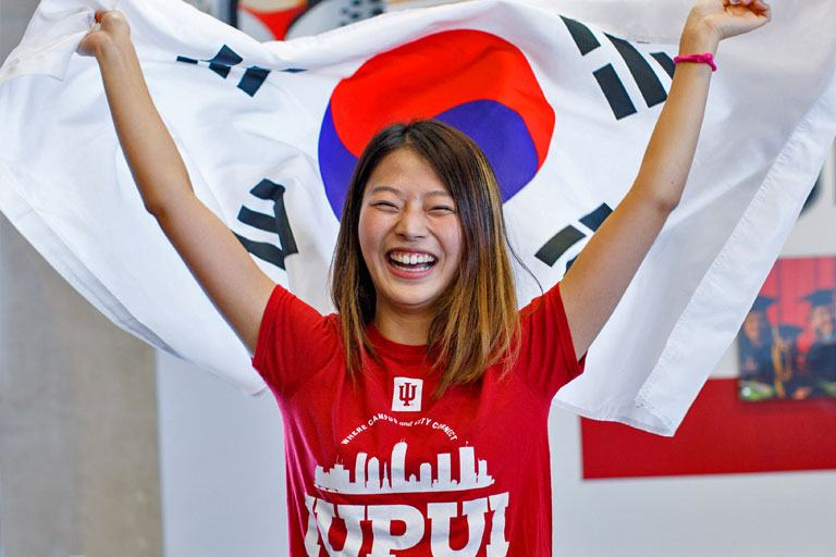 An international student holds a South Korean flag